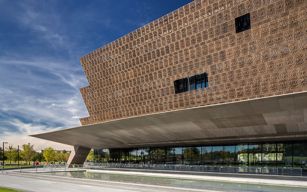 An exterior view of The National Museum of African American History & Culture building. It has three layers of brown tiles with a concrete awning look at the bottom that jets upward.